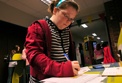 Debra, 10, fills out her deposit slip before heading to the teller to receive her check and debit card.