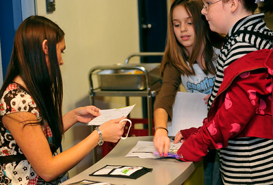 An ISU student helps Ashton, 11, and Debra, 10, organize their money and bank statement into pouches.