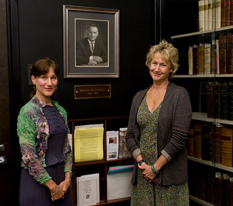 Barbara Cordell and Jeanne Shafer pose with a photo of their father Warren Cordell in the Cordell Collection room.