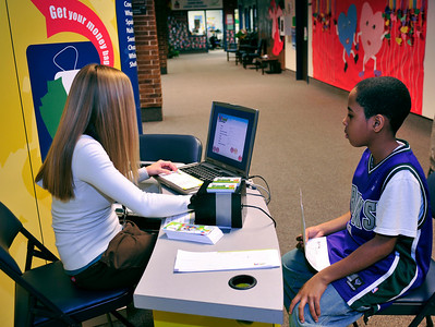 Bryson, 10 works with the teller to get his checking and savings accounts set up.